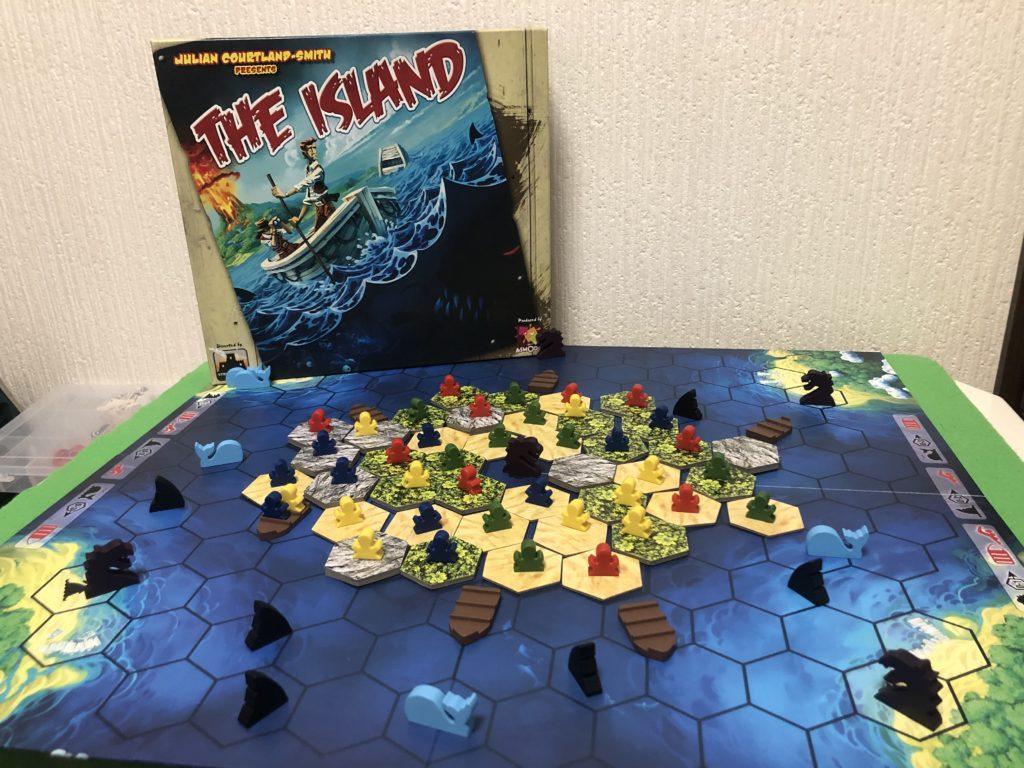 ボードゲーム『アイランド』の全体画像。島タイルの上に人駒が乗り、広い海には様々な怪物がうごめいている様子