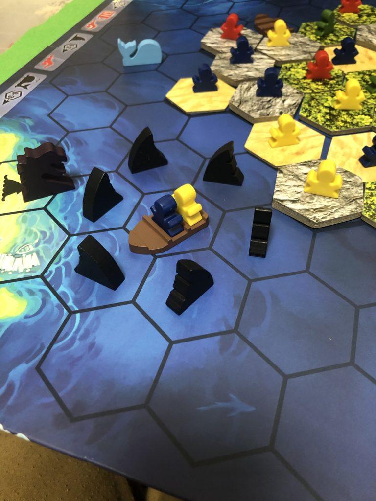 海マップの上に孤立する船駒とその上に乗る人駒、更に青の周りを囲むサメ駒たち