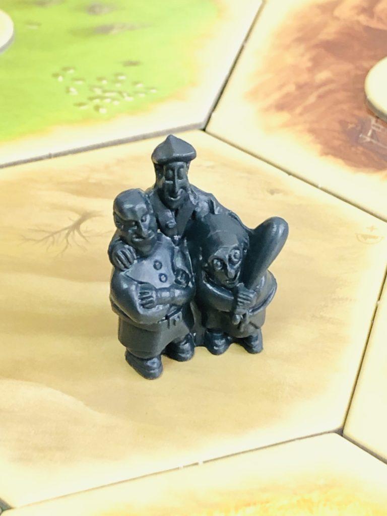 ボードゲーム『カタン』の盗賊駒。砂漠のボードの上に黒い人型の駒が乗っている画像