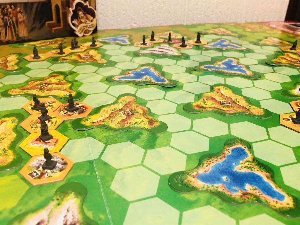 ボードゲーム『ラチッタ』の盤面画像。広くきれいな地図状のボードの上に地形や町、市民が息づいている様子