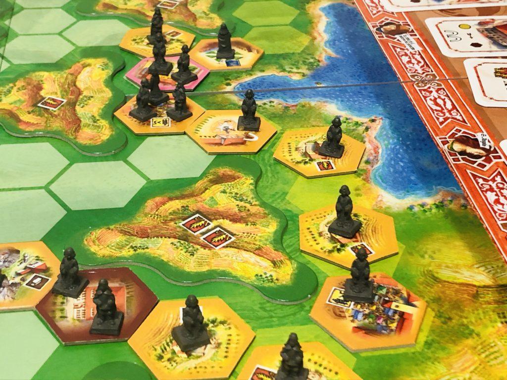 ボードゲーム『ラチッタ』の盤面解説画像。細かいタイルの上に市民コマが乗っている