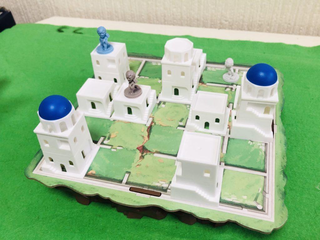 ボードゲーム『サントリーニ』のプレイ中の様子。立体ボードに白い建物駒の並んだ美しい盤面