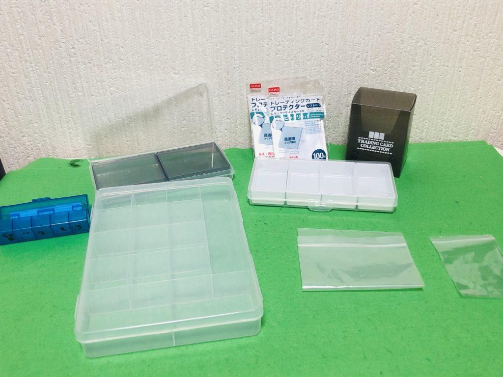 100均の収納小物を並べた画像。緑色のテーブルマットの上に小物入れやジッパーバッグが並べられた画像