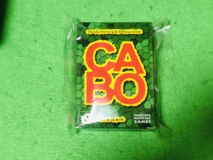 緑のマットの上に緑のパッケージのボードゲームが乗っている画像