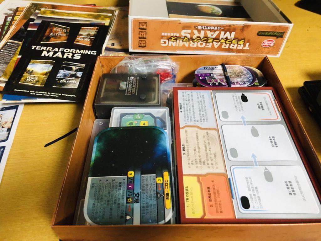 ボードゲーム『テラフォーミングマーズ』の箱の中身。大きめのボードやタイルが詰め込まれている